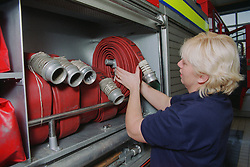 Part time female firefighter placing fire hose in side of fire engine,