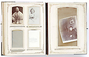 open vintage family photo album from late 1800s and later with portraits and missing photographs