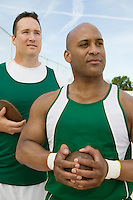 Two male athletes holding shot and discus