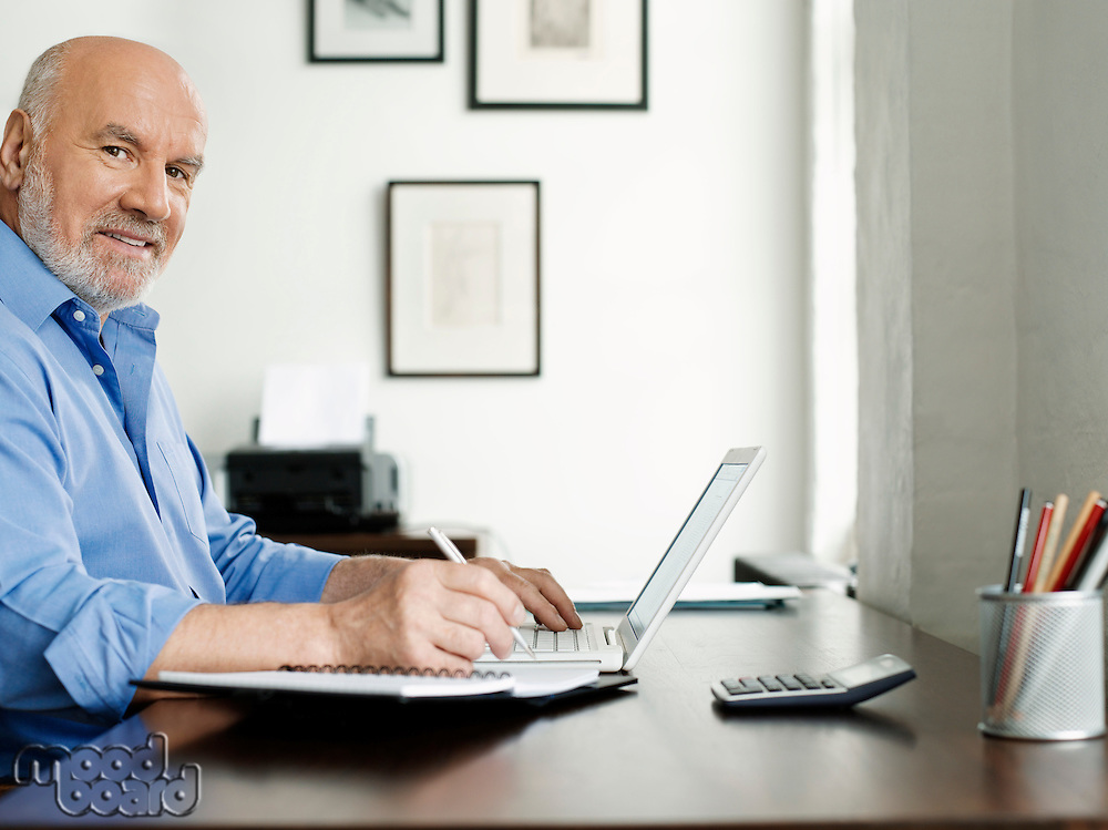 Middle-aged man sitting at desk using laptop and writing in notepad