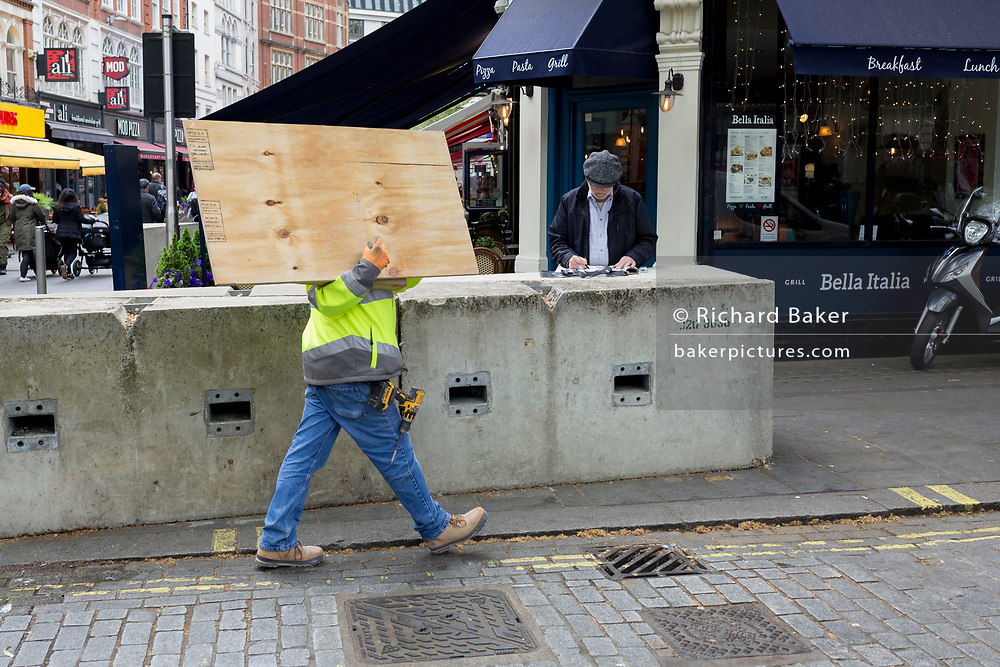 With face obscured, a workman carries wooden board supplies past concrete anti-terrorism security blocks off Leicester Square in the West End, on 29th April 2019, in London, England.