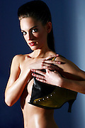Topless female model in her 20s with hand bag, studio