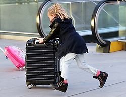 An excited youngster rushes to the check in at London Gatwick airport as the Christmas getaway starts Friday, 20th December 2013. Picture by Stephen Lock / i-Images