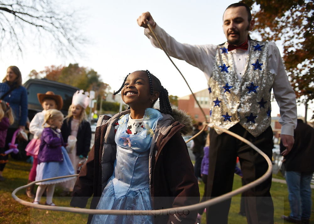 Nevai Taylor, of Roslindale, is lassoed by Smyly the Juggler during the Boston Police Dept.'s 12th annual Halloween party, held at the Boston Police District E-5 station in West Roxbury, Friday, Oct. 30, 2015.<br /> Wicked Local staff photo / Kate Flock