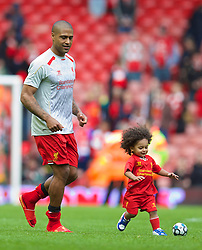 LIVERPOOL, ENGLAND - Sunday, May 11, 2014: Liverpool's Glen Johnson with one of his sons on the pitch after the Premiership match at Anfield. (Pic by David Rawcliffe/Propaganda)