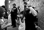 Darian Edwards makes a grab for Det. Jim Mingle's hat while he and Det. Thomas Stoner walk the beat at Poe Homes public housing on West Lexington Street in Baltimore. As crime mounts in the city, Mayor Sheila Dixon ordered detectives and other non-uniformed officers to start walking foot patrols.<br /> <br /> A group of local children had gathered around the two detectives as they investigated reports of fireworks in the area.