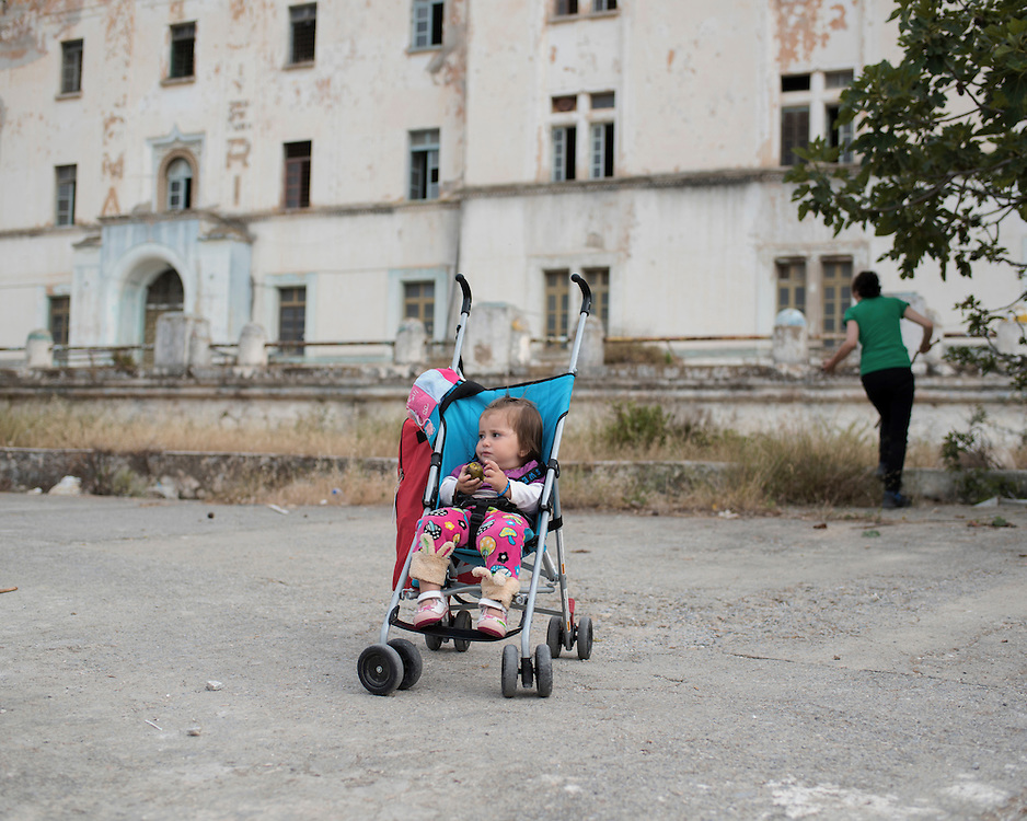 14 month old Yazidi girl Asma Aisam Ismail outside the abandoned Lepida psychiatric hospital in whose grounds the Leros &lsquo;Hot spot&rsquo; (an EU-run migrant&rsquo;s reception centre) has been built. Her mother, Torko Haji Khalaf, 21, picks figs in the background. <br />