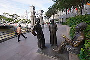 Singapore. Cavenagh Bridge and statues depicting life in old Singapore.
