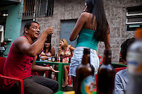 Residents hang out during a birthday party in the streets of a community in Complexo da Mare, Rio de Janeiro, Brazil, on Saturday, April 27, 2013. Complexo da Mare, is a complex of 16 communities, in the north zone of Rio de Janeiro. It is the largest complex of favelas with 130,000 residents. It is targeted for pacification as the city prepares for the 2014 World Cup and the 2016 Olympics. Four factions run the complex -  three drug gangs and the militia. The rival gangs fight for control of the drug trade. Although crime is low in the favelas by rule  of law enforced by the gangs, cross-fire shootings and gang violence is often high. Neighborhood associations are an integral part of community development within Mare, making up for a lack of government assistance.