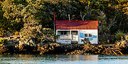 A lone cottage situated on the western entance to Islington Bay, Hauraki Gulf, Auckland.