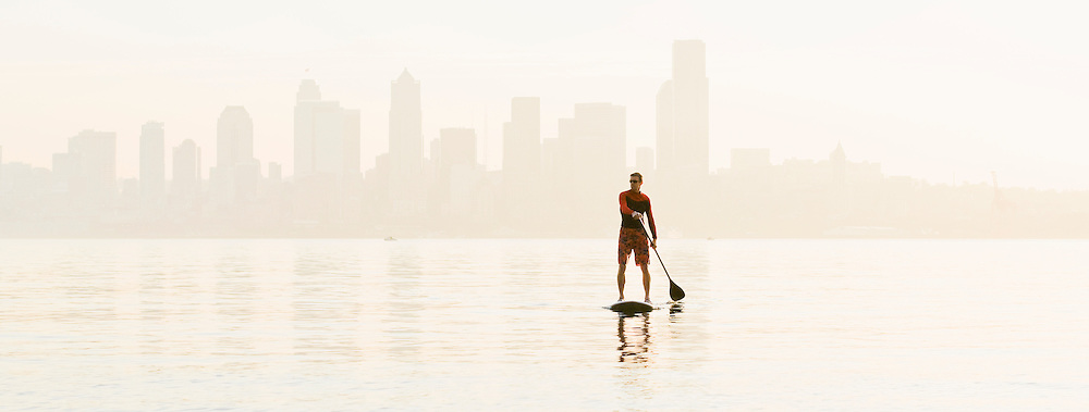 A man paddling on his stand-up paddle board on Elliott Bay with the Seattle skyline in the background.