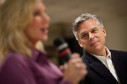 Republican presidential candidate Gov. Jon Huntsman listens as his wife Mary Kaye Huntsman introduce him to republican supporters at a breakfast event on December 3, 2011 in Goose Creek, South Carolina.