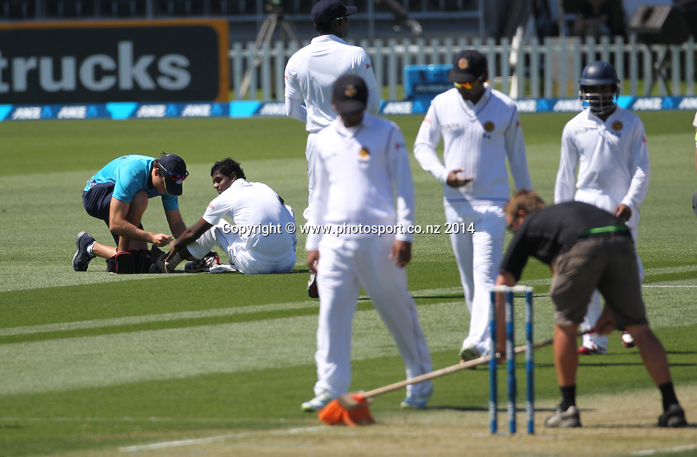 Shaminda Eranga of Sri Lanka has some treatment on his ankle after falling while bowling the first ball of his first over on Day 1 of the boxing Day Cricket Test Match  the Black Caps v Sri Lanka at Hagley Oval, Christchurch. 26 December 2014 Photo: Joseph Johnson / www.photosport.co.nz