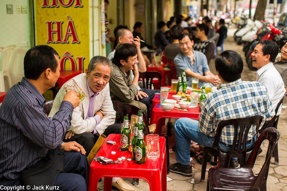 "30 MARCH 2012 - HANOI, VIETNAM:   Men drink beer at a sidewalk cafe and beer bar in Hanoi, Vietnam. Beer, called ""bia"" in Vietnamese, costs about .20¢ US per glass at the sidewalk beer bars.  PHOTO BY JACK KURTZ"