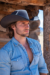 good looking cowboy in a denim shirt by a rustic cabin