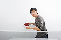Handsome Asian man playing ping pong