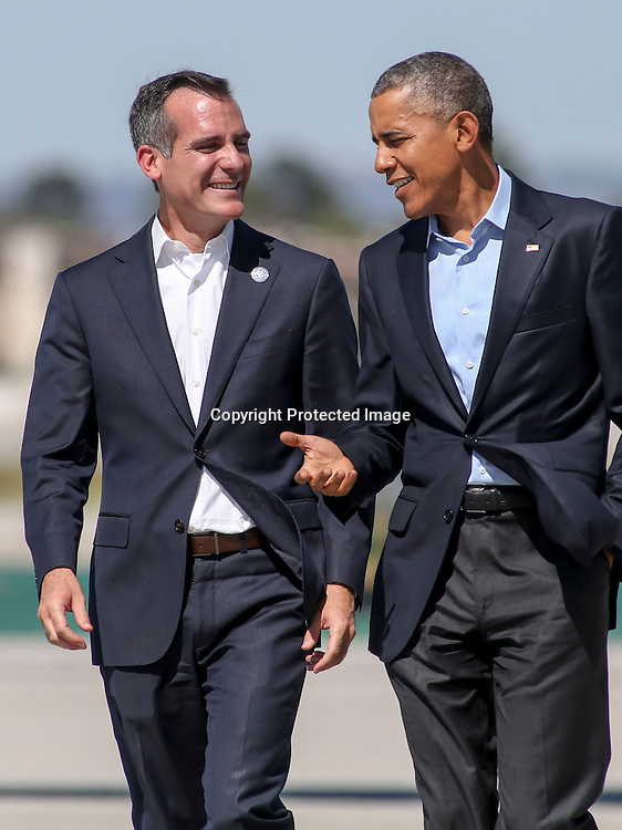 President Barack Obama, right, is greeted by Los Angeles Mayor Eric Garcetti, left, as he arrives on Air Force One at Los Angeles International Airport in Los Angeles on Saturday, Oct. 10, 2015. (AP Photo/Ringo H.W. Chiu)