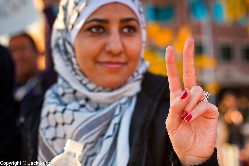 "31 JANUARY 2011 - TEMPE, AZ: A woman flashes a ""peace"" during a demonstration in Tempe, AZ, supporting democracy in Egypt About 200 people marched through central Tempe, AZ, near the Arizona State University campus Monday afternoon. The rally was organized by the Arab American Association of Arizona in solidarity with the ongoing pro-democracy rallies and demonstrations in Egypt and other Arab countries.    Photo by Jack Kurtz"