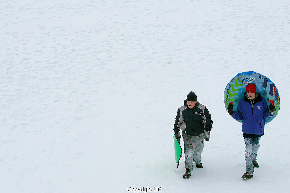 Tommy Spengler, 12, (L) and brother Nate Spengler, 15, of Rockland Massachusetts, walk up a hill while sledding in their home town on December 27, 2010.  The area was hit by a blizzard which dumped over a foot and a half of snow in other parts of the state and caused coastal flooding.   UPI/Matthew Healey