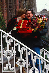 couple carrying many Christmas presents on the stairs of a brownstone building in New York City
