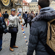 A street vendor shows his wares to tourists on the edge of the old town square at the heart of Prague, capital of the Czech Republic, on 10 November 2014.