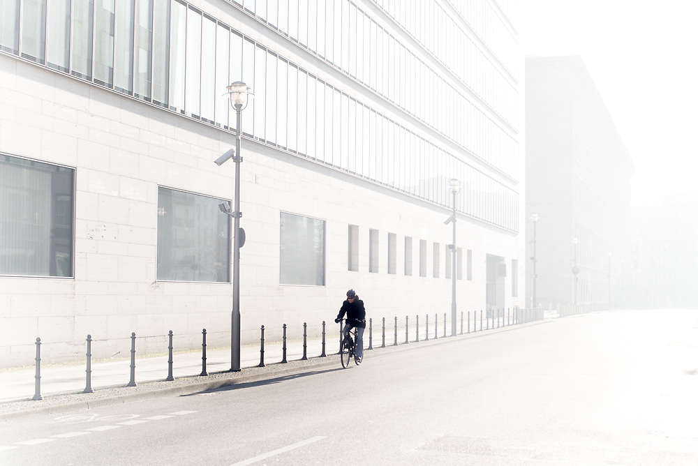 A cyclist washed by morning sunlight in a street of Berlin.