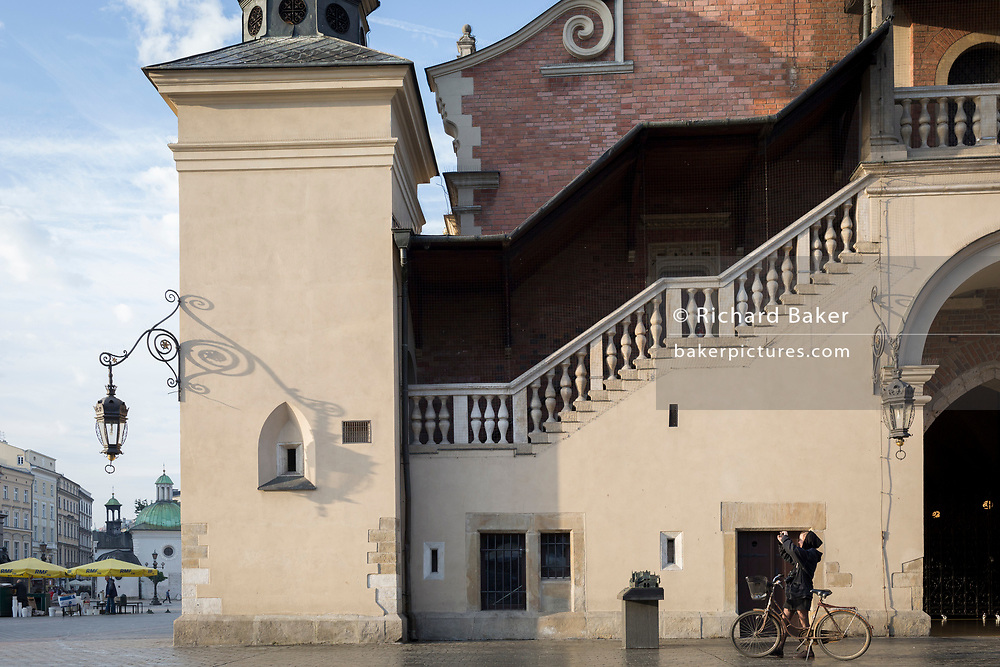 A lady cyclist stops outside the Cloth Hall to photograph architecture and scenes on Rynek Glowny market square, on 23rd September 2019, in Krakow, Malopolska, Poland.