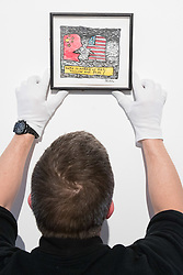 Christies, St James, London, March 4th 2016. A gallery technician hangs Derek Boshier's &quot;Who Is Afraid Of Red, Yellow and Blue (II), in watercolour and black ink at the preview for the It&rsquo;s Our World charity auction at Christie's. Over 40 leading artists including David Hockney, Sir Antony Gormley, David Nash, Sir Peter Blake, Yinka Shonibare, Sir Quentin Blake, Emily Young and Maggi Hambling have committed artworks to the It&rsquo;s Our World Auction in support of The Big Draw and Jupiter Artland Foundation, to be sold at Christie&rsquo;s London on 10 March 2016.<br />  ///FOR LICENCING CONTACT: paul@pauldaveycreative.co.uk TEL:+44 (0) 7966 016 296 or +44 (0) 20 8969 6875. &copy;2015 Paul R Davey. All rights reserved.