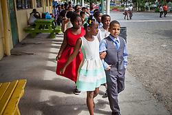 Janiel Montanez, right, escorts partner Jayda Bartlett into the ballroom at Ricardo Richards Elementary School.  17 December 2015.  Christiansted, St. Croix.   © Aisha-Zakiya Boyd.
