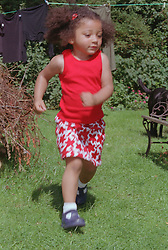 Young girl running in garden,