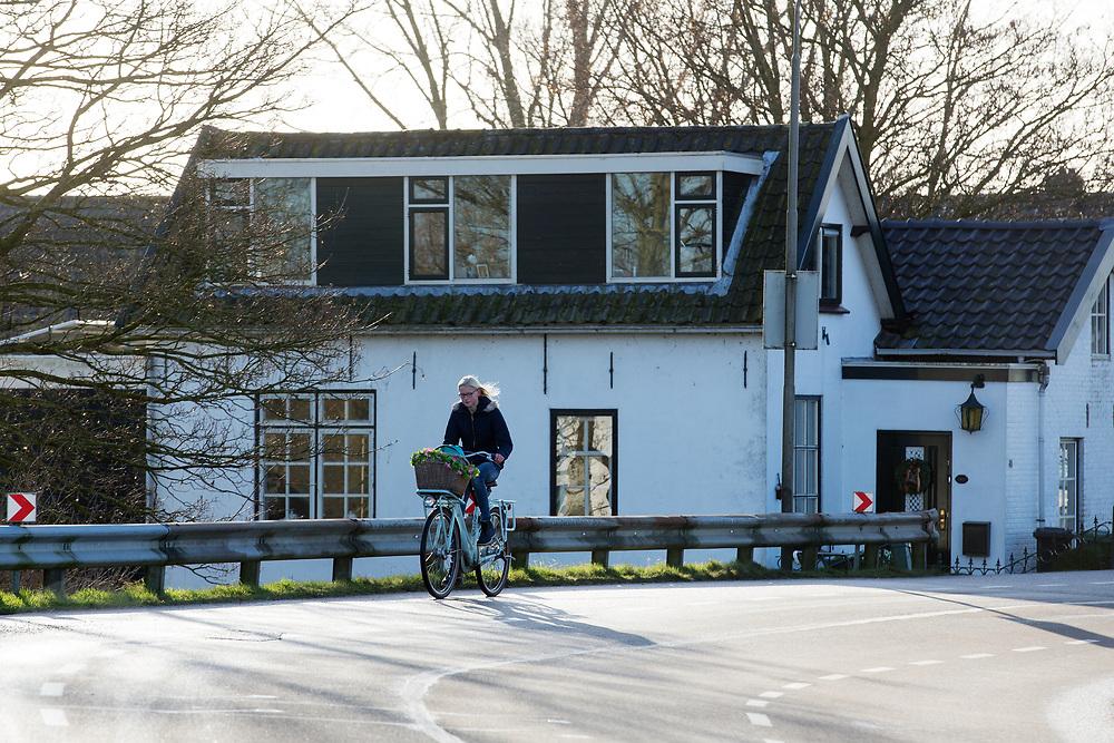 In Ouderkerk aan de IJssel rijden fietsers over de dijk.<br /> <br /> In Ouderkerken aan de IJssel cyclists ride at a dike.