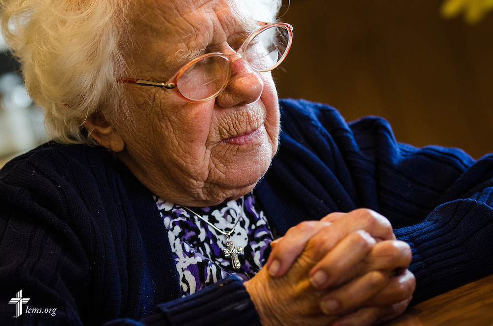 A 103 year-old church member prays at her home while the Rev. Harold Block, visitation pastor at St. Paul's Lutheran Church, visits with her outside Concordia, Mo., on Thursday, April 10, 2014. LCMS Communications/Erik M. Lunsford