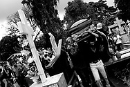 Family and friends carry Maximo's remains to his family's burial tomb in the local cemetery. Maximo was fatally shot outside of his cousins' home in Belen, a red zone heavily controlled by Colombian narco-traffickers. Police investigators have not solved nor do they claim to have any leads on Maximo's murder.  His case, like the majority of other red zone killings in Belen, will most likely go unsolved. Police corruption and incompetence often leads families to resort to taking justice into their own hands, perpetuating street violence in their community.