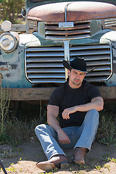hot cowboy sitting against an old vintage truck