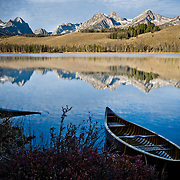 Little boat on lake with mountains in background