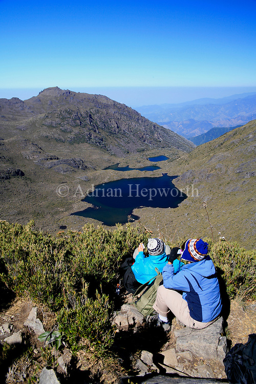 Tourists looking at Lake Chirripo from the summit of Mount Chirripo, Costa Rica's highest mountain (3820m). Chirripo National Park, Costa Rica.<br /> <br /> For pricing click on ADD TO CART (above). We accept payments via PayPal.