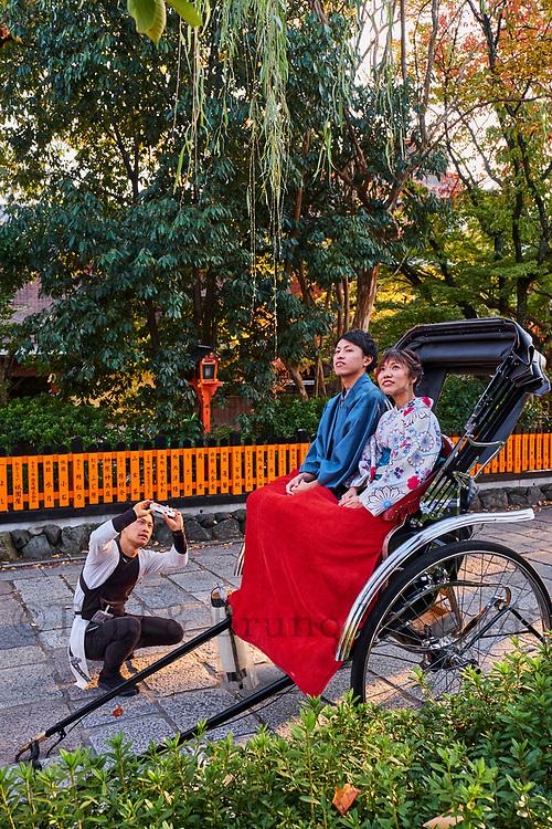 Japon, île de Honshu, région de Kansaï, Kyoto, Gion, ancien quartier des Geishas, couple de touristes en kimono se promenant en pousse-pouss // Japan, Honshu island, Kansai region, Kyoto, Gion, Geisha former area, couple in kimono travelling with local taxi