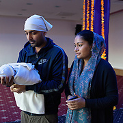 Slough, Greater London, UK, January 24, 2015. Ramgharia Sikh Gurdwara Temple.<br /> Four days after the birth of their first child, Taminder and Kamaljit present their boy at the Temple. The mother and father are quite proud and happy.
