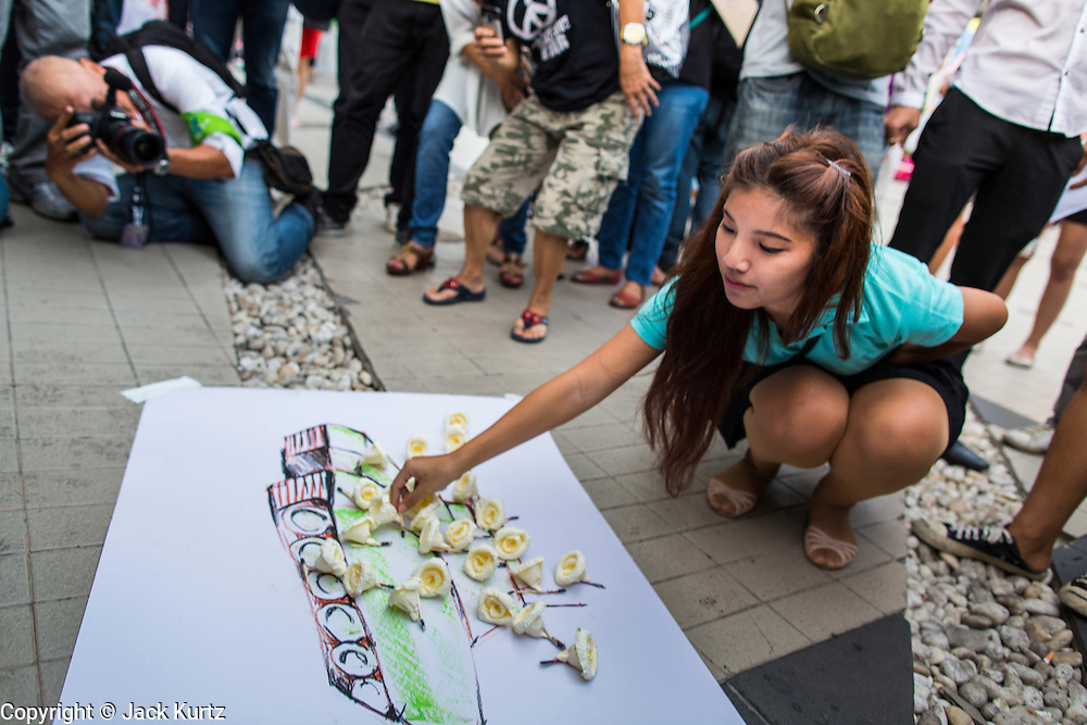20 MAY 2014 - BANGKOK, THAILAND: Thai anti-martial law protestors put dried roses on a drawing of an army tank. About 200 Thais gathered at the Bangkok Art and Culture Centre in central Bangkok to protest the army's decision to impose martial law.   PHOTO BY JACK KURTZ