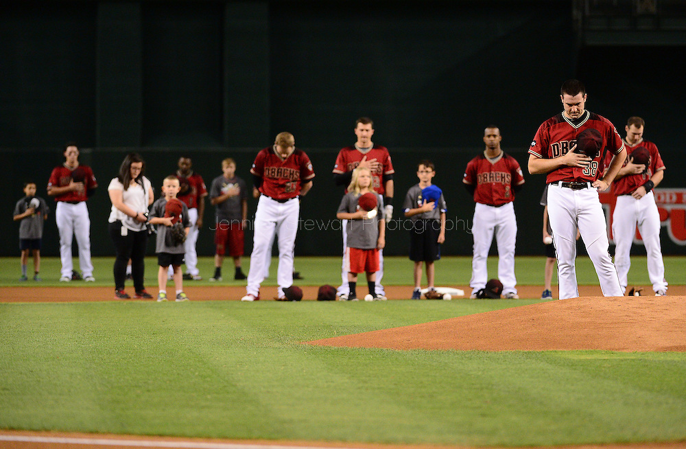 PHOENIX, AZ - JUNE 12:  Robbie Ray (R) of the Arizona Diamondbacks and the starting lineup stand for a moment of silence for the victims in the Pulse nightclub terror attack in Orlando prior to the MLB game against the Miami Marlins at Chase Field on June 12, 2016 in Phoenix, Arizona.  (Photo by Jennifer Stewart/Getty Images)