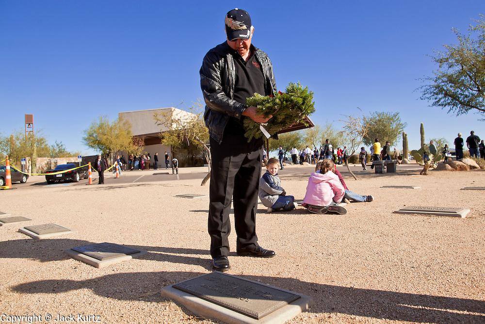 09 DECEMBER 2011 - PHOENIX, AZ:  ROBERT BELLMAN lays a Christmas wreath on a veteran's grave in Phoenix Saturday. Bellman and his wife bought 15 years wreaths this year for graves. They've been participating in the wreath laying ceremony for years. Several hundred volunteers and veterans gathered at the National Memorial Cemetery of Arizona in Phoenix Saturday to lay Christmas wreaths on headstones, a tradition started by Wreaths Across America. Wreaths Across America is a nonprofit organization founded to continue and expand the annual wreath laying ceremony at Arlington National Cemetery begun by Maine businessman, Morrill Worcester, in 1992.   PHOTO BY JACK KURTZ