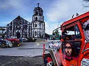 21 JANUARY 2018 - LEGAZPI, ALBAY, PHILIPPINES: A Jeepney parked in front of Our Lady of the Gate Parish in Legazpi. The church, built in 1773, was known by its Spanish name, Parroquia Nuestra Señora de la Porteria, before the American colonization of the Philippines.     PHOTO BY JACK KURTZ