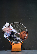 Jack Wolfinger jams the ball while playing around at the park on the North Park Blocks in Portland. A promising basketball player, he let distractions take him away from the game. he's now working hard to get back his game.