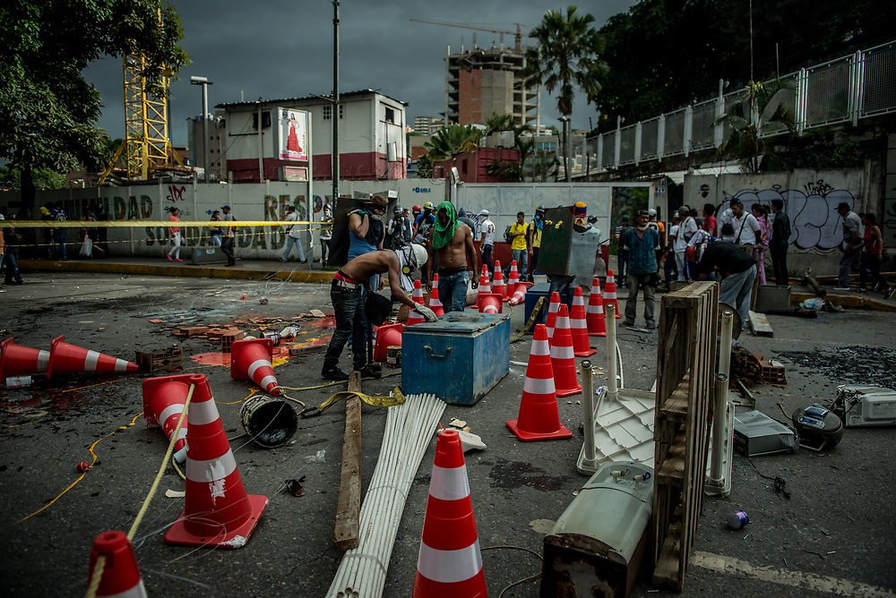 CARACAS, VENEZUELA - MAY 24, 2017:  Anti-government protesters broke into and looted materials from an Odebrecht construction supply hub to build a road block.  Millions of dollars have been stolen from state coffers  through corrupt politicians' shady dealings with Odebrecht.   The streets of Caracas and other cities across Venezuela have been filled with tens of thousands of demonstrators for nearly 100 days of massive protests, held since April 1st. Protesters are enraged at the government for becoming an increasingly repressive, authoritarian regime that has delayed elections, used armed government loyalist to threaten dissidents, called for the Constitution to be re-written to favor them, jailed and tortured protesters and members of the political opposition, and whose corruption and failed economic policy has caused the current economic crisis that has led to widespread food and medicine shortages across the country.  Independent local media report nearly 100 people have been killed during protests and protest-related riots and looting.  The government currently only officially reports 75 deaths.  Over 2,000 people have been injured, and over 3,000 protesters have been detained by authorities.  PHOTO: Meridith Kohut
