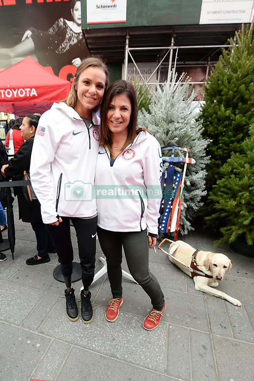 Skiing Paralympians Oskana Masters,  Danelle Umstead, and Danelle's guide dog Aziza, pose during the Team USA Winter Fest  - 100 day countdown to the 2018 Winter Olympics, in Times Square, New York, on November 1, 2017. (Photo by Anthony Behar/Sipa USA)