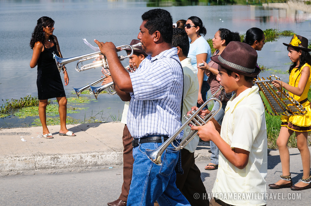 A band plays as part of the celebrations for Guatemalan Independence Day on September 15, 2011. Groups of school students parade in a procession through the streets of Flores, starting in the Parque Central, walking through the town, and crossing the causeway into Santa Elena.