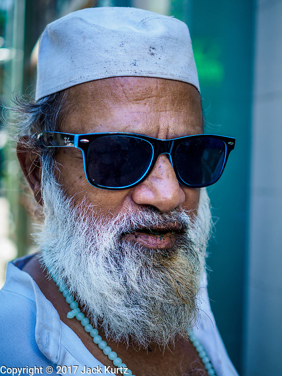 "24 NOVEMBER 2017 - YANGON, MYANMAR: A Muslim man waits to enter Surtee Sunni Jumma Mosque for Friday midday prayers. Many Muslims in overwhelmingly Buddhist Myanmar feel their religion is threatened by a series of laws that target non-Buddhists. Under the so called ""Race and Religion Protection Laws,"" people aren't allowed to convert from Buddhism to another religion without permission from authorities, Buddhist women aren't allowed to marry non-Buddhist men without permission from the community and polygamy is outlawed. Pope Francis is to arrive in Myanmar next week and is expected to address the persecution of the Rohingya, a Muslim ethnic minority in western Myanmar. Some Muslims and Christians are concerned that if the Pope's comments take too strong of pro-Rohingya stance, he could exacerbate religious tensions in the country.  PHOTO BY JACK KURTZ"