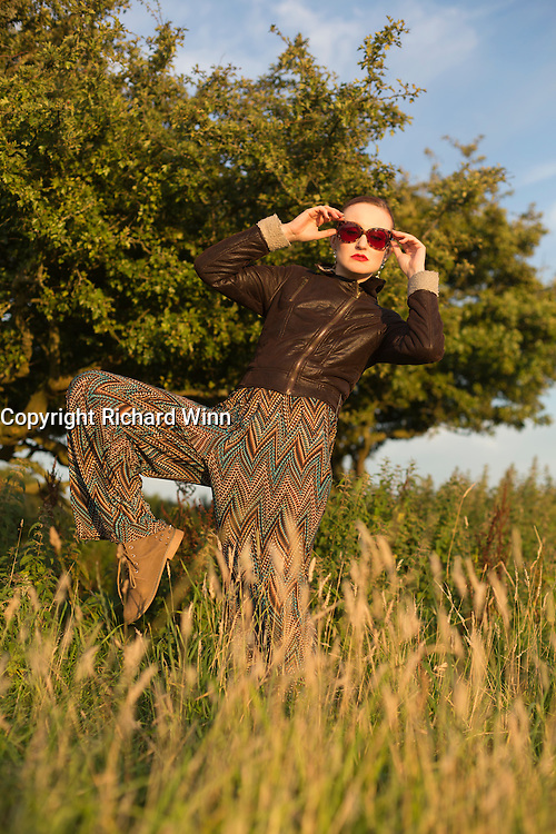 Woman in 1970's style clothing standing on one leg in front of a tree on Draycott Sleights in the late evening sun.