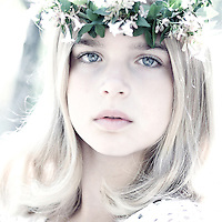 Female child with blonde hair wearing headband of small white flowers looking at camera