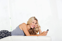 Portrait of young woman with cell phone lying
